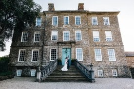 WIDE ANGLE SHOT OF KINGSTON ESTATE WITH A NEWLY WED COUPLE AT THE TOP OF THE STAIRS.