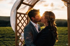 SUNSET SHOT OF A WEDDING COUPLE KISSING.