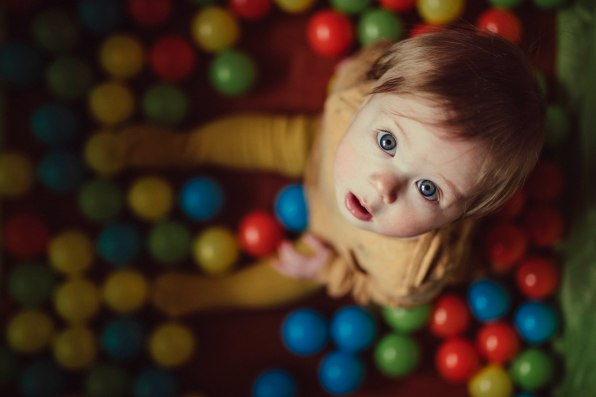 Birdseye view of a little baby girl in a coloured ball pit