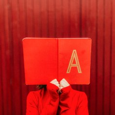 Part of the Childhood Treasures Editorial Series. A girl in red holds a red notebook infront of her face that has an A on it. She stands infront of a red backdrop.