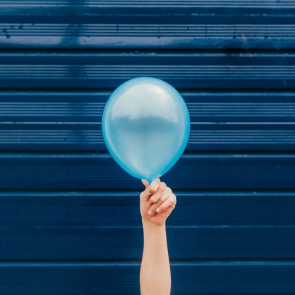 Part of the Childhood Treasures editorial series. A single hand holds up a blue balloon vertically infront of a blue garage door.