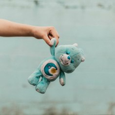 Part of the Childhood Things editorial series. A single hand holds a blue Care Bear teddy.