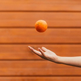 From the Childhood Treasures series - a single hand throws and orange in the air infront of an orange background