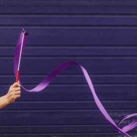 Part of the Childhood Treasures editorial series. A single hadn loops a gymnastic purple ribbon infront of a purple backdrop.