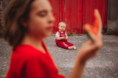 Two girls eat watermelon in the alley way both wearing red in front of a red garage door. The older girl in the foreground frames the younger girl.
